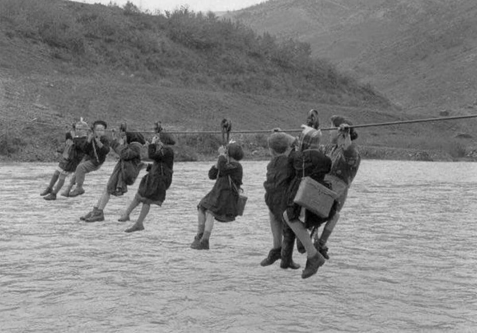 Esta foto mostra como crianças nos arredores de Modena, Italia, iam para a escola. Elas precisavam atravessar o rio usando roldanas no deslocamento. 1959.