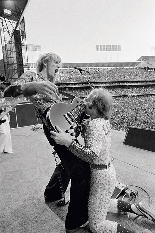 Elton John durante show no Dodger Stadium, EUA, com o guitarrista Davey Johstone, em 1975.