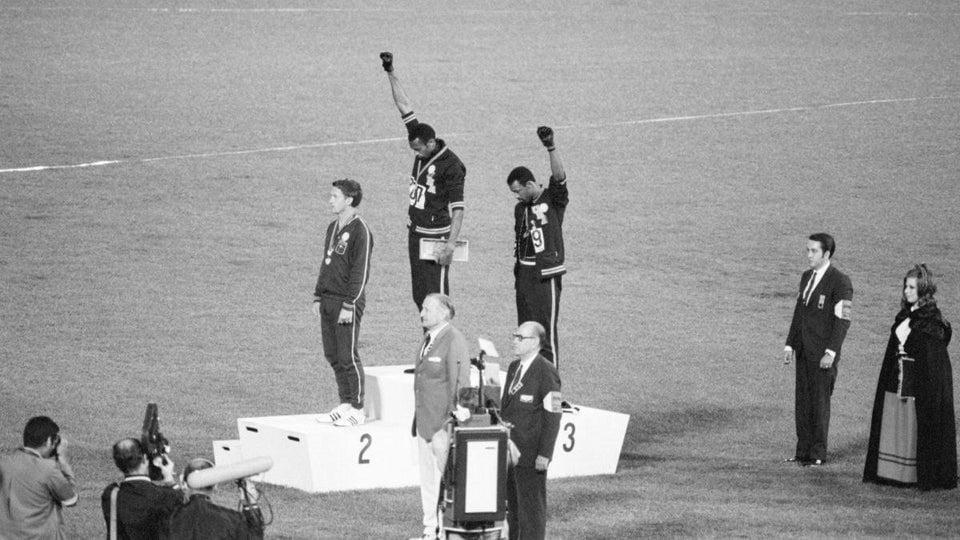 Nas Olimpíadas de 1968, Tommie Smith e John Carlos levantam seus punhos em saudação Black Power para destacar a desigualdade racial nos Estados Unidos.