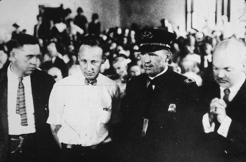 O professor do segundo grau John T. Scopes é levado a julgamento em Dayton, Tennessee, por ensinar a teoria de evolução, que era proibida pela lei estadual, em 10 de julho de 1925.