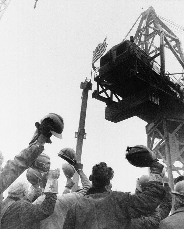 Trabalhadores da construção erguem seus chapéus em saudação à banderia americana afixada no topo do World Trade Center, em 1973.