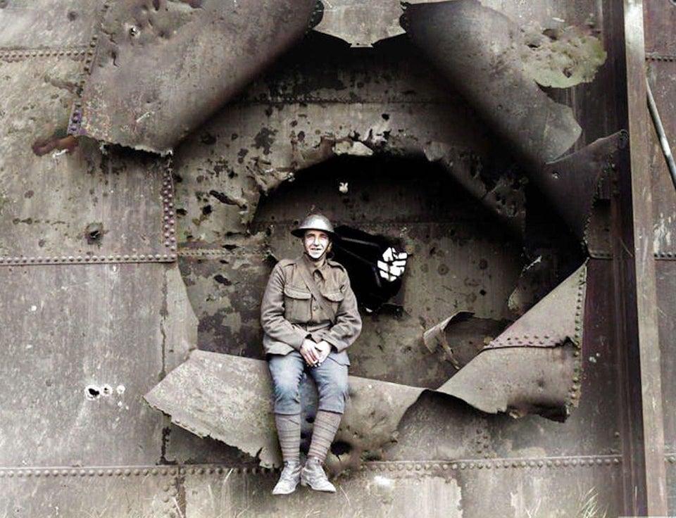 Soldado britânico sentado no buraco de bomba em um gasômetro em Nieuport, companhia francesa fabricante de aviões, em 1917.