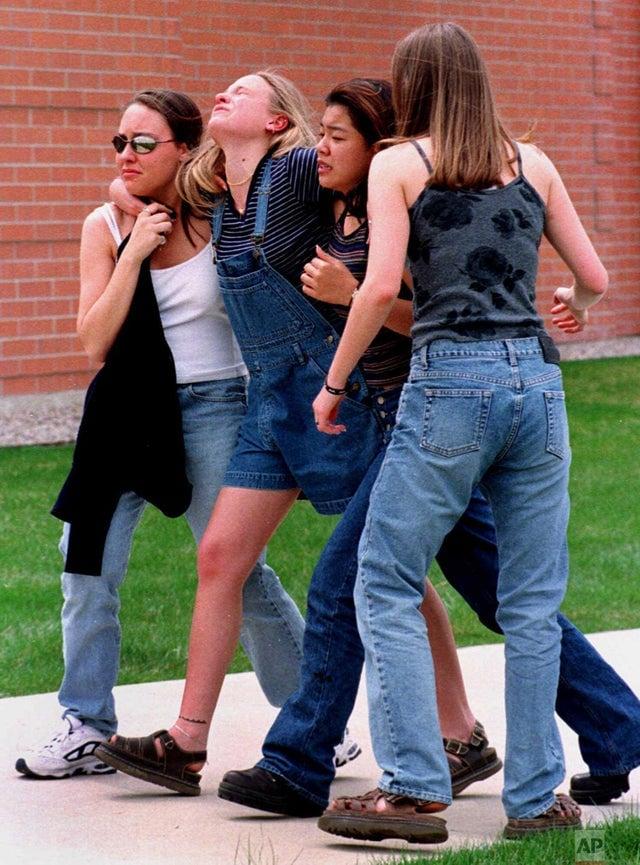 Alunos sobreviventes do massacre na Escola Secundária de Columbine dirigindo-se a uma biblioteca onde professores e outros alunos se reuniram para escapar dos assassinos que invadiram a escola. Em 20 de abril de 1999.