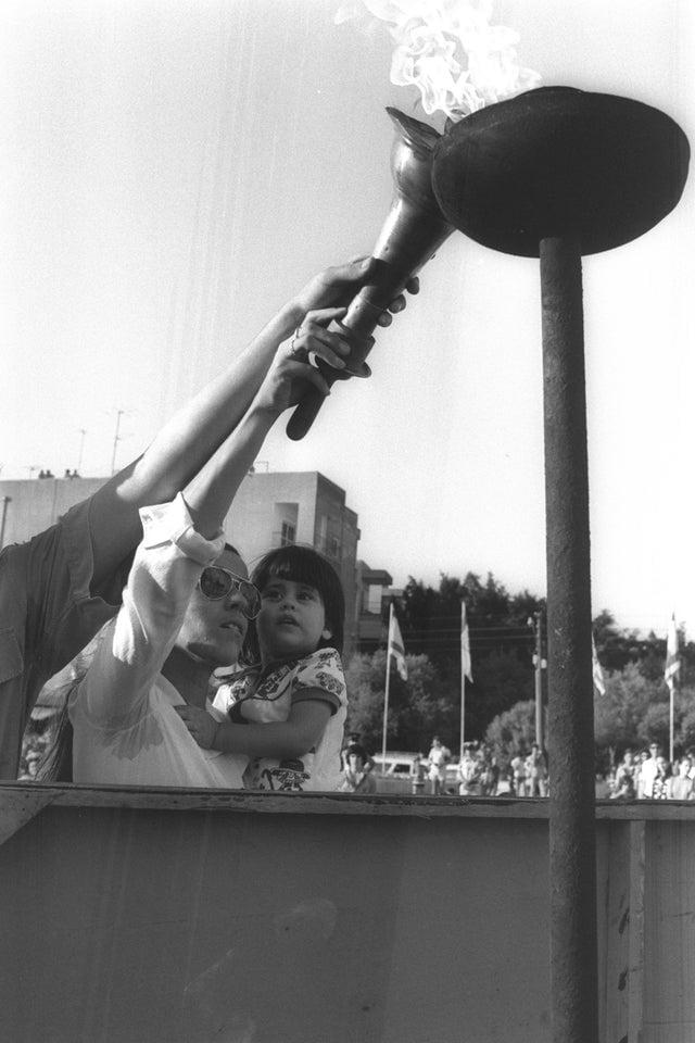 A viúva de Andre Spitzer, um dos 11 atletas israelenses massacrados em Munique, segurando sua filha enquanto acende a tocha durante cerimônia memorial na praça Yud Alef, 1974.