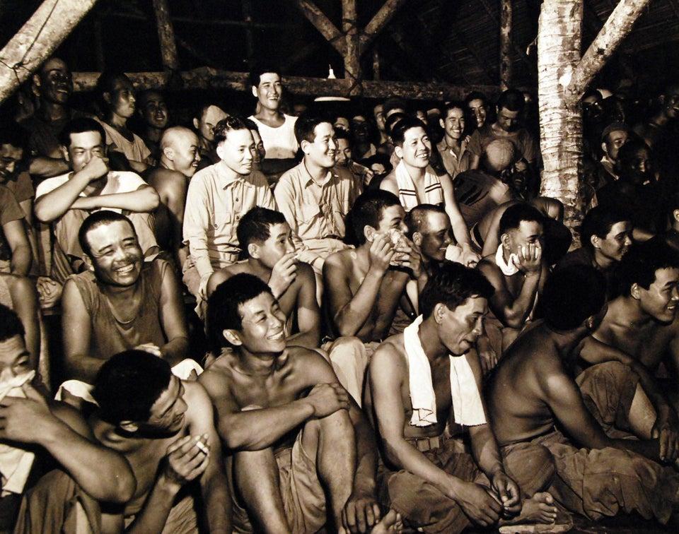 Prisioneiros de guerra japoneses assistindo a um show de comédia conduzido por outros prisioneiros de guerra, em Guam, agosto de 1945.