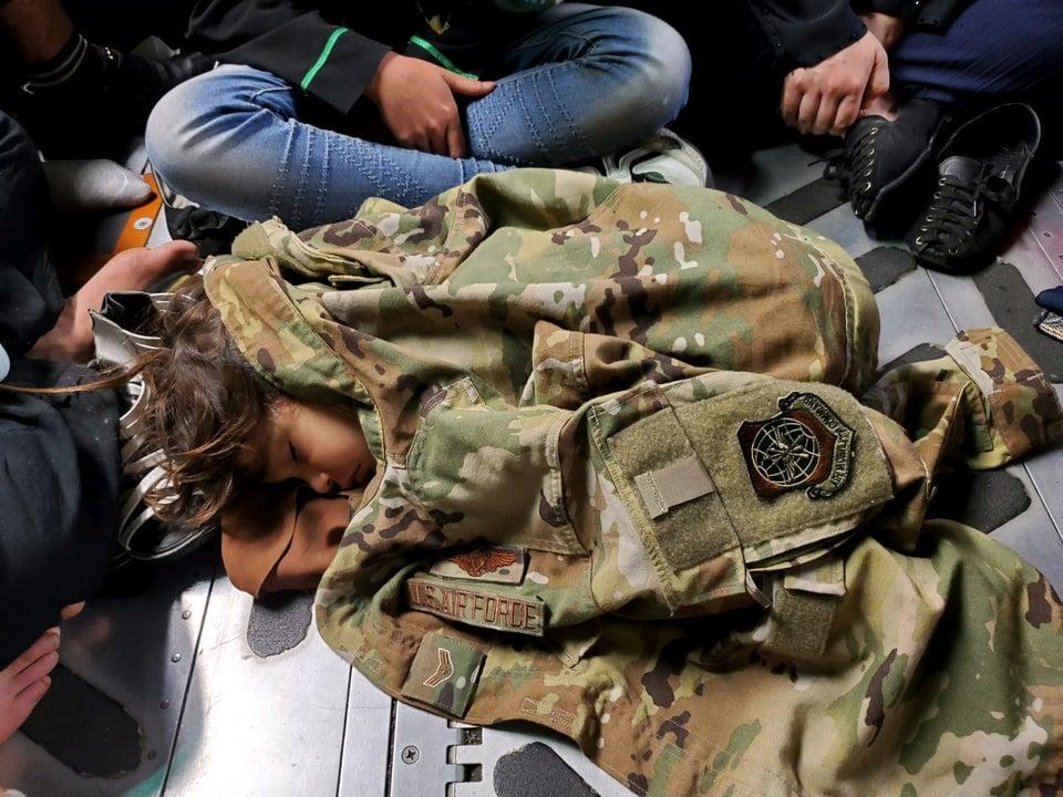 Criança afegã dorme no piso de um C-17 Globemaster III aquecida pelo uniforme de um soldado durante vôo de evacuação de Cabul, Afeganistão, em 15 de agosto de 2021.