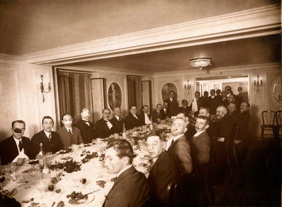 Jantar para soldados franceses com graves lesões faciais recebidos durante a Primeira Guerra Mundial, realizado por Henri Manuel em 1925.