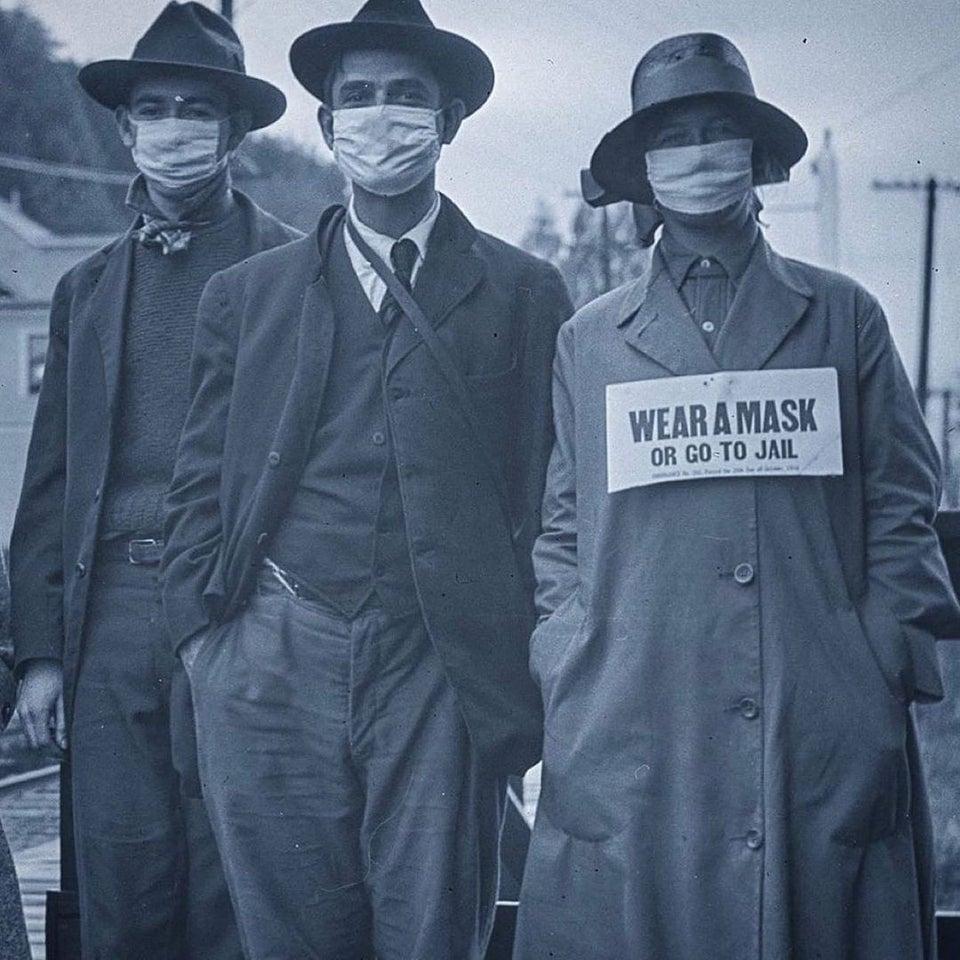 Três pessoas com máscara posando para foto durante a segunda onda da Gripe Espanhola, na Califórnia, em 1918.