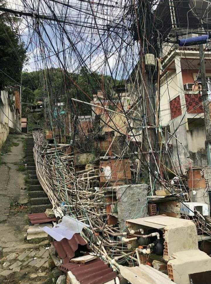 Foto tirada no complexo de favelas do Lins, na zona norte do Rio de Janeiro. Moradores instalam canos e fios para fazerem água e energia chegarem a suas casas no alto do morro.