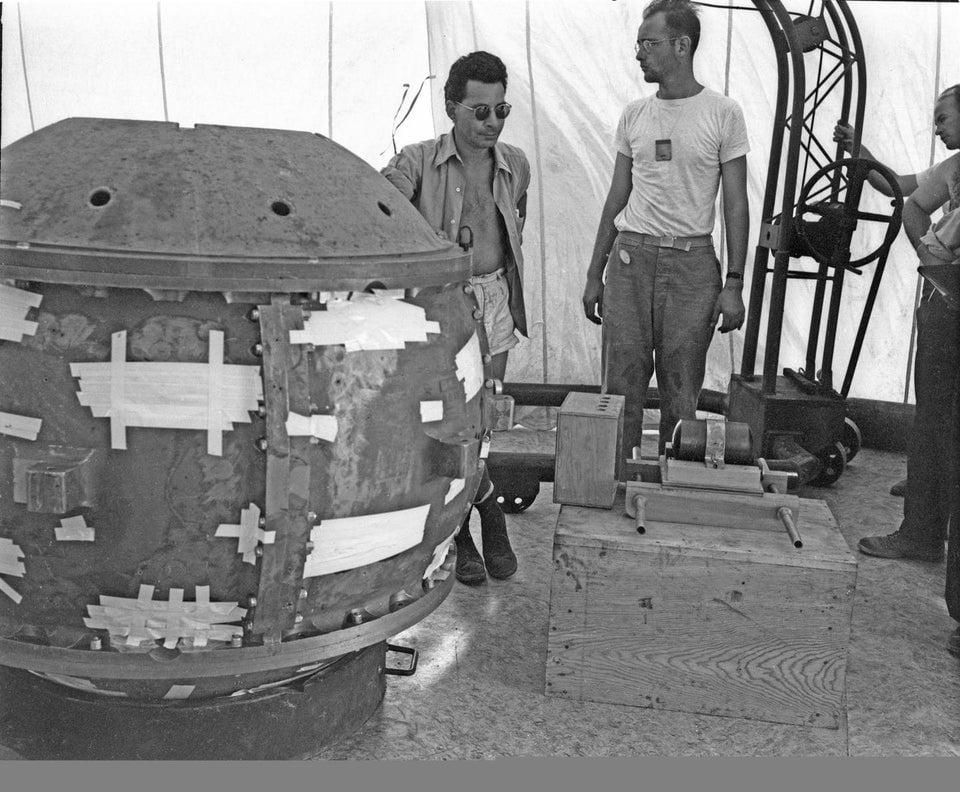 O físico Louis Slotin com a bomba Gadget durante teste. Ele foi morto um ano depois em decorrência de queimaduras causadas pela exposição a material radioativo quando sua chave de fenda escorregou durante um experimento, 1945.