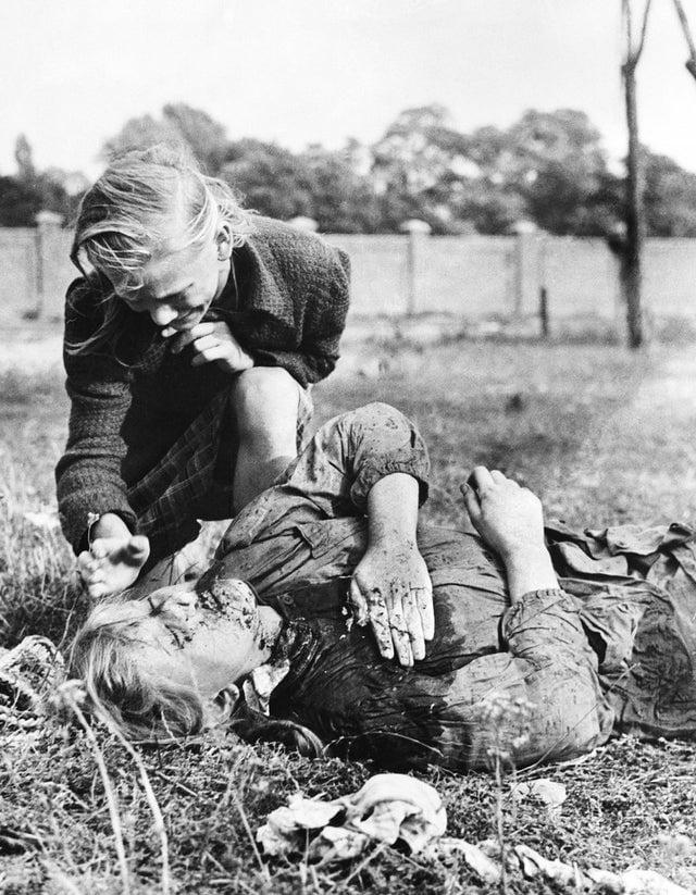 Menina polonesa de 12 anos ajoelhada sobre o corpo de sua irmã que foi morta durante bombardeio de nazistas, em 9 de setembro de 1939.