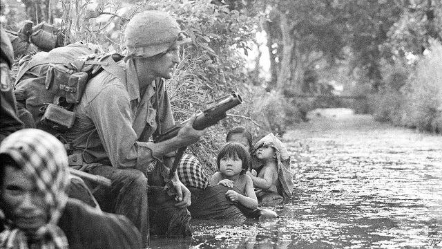 Soldado americano de guarda nas selvas do Vietnã segurando um lançador de granadas. Ao seu lado, um grupo de mulheres e crianças obviamente assustado - 1960.